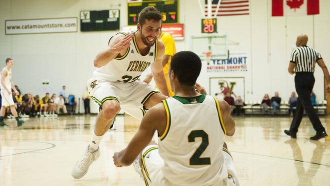Catamounts forward Ethan O'Day (32) helps up Trae Bell-Haynes (2) were both named to the America East all-league third team. Kurt Steidl also earned third-team honors, while Ernie Duncan (all-rookie) and Dre Wills (all-defensive) were also lauded.