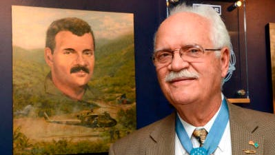 Retired Air Force Col. James P. Fleming, 73, poses Tuesday at the unveiling of his portrait on the 58th Special Operations Wing's Medal of Honor Wall at Kirtland Air Force Base.