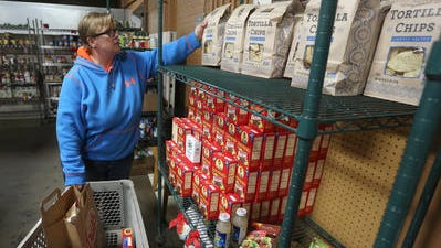 A volunteer gets food ready that will delivered to a family in need December 23, 2014, at The Neighbors' Place in Wausau.