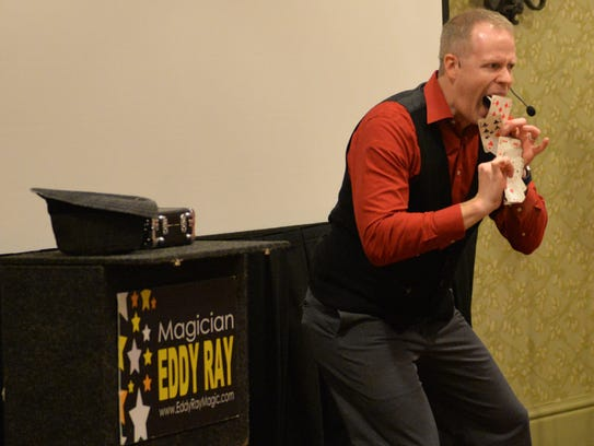 Magician Eddy Ray performs a card trick during a show