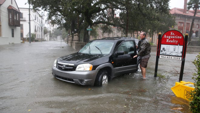 A man prepares to leave a flooded street as Hurricane Matthew moves along  the coast on Oct. 7, 2016, in St. Augustine , Fla.