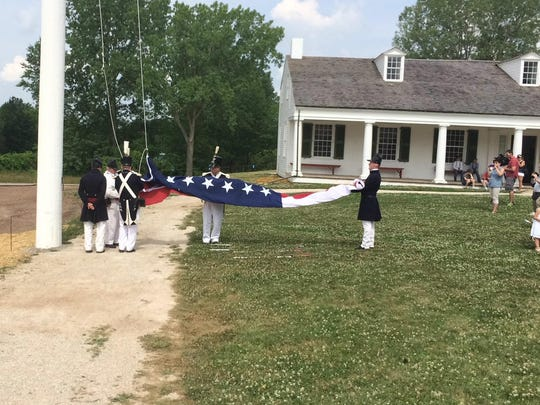 A 19th-century honor guard prepares to raise a flag over Heritage Hill's new guardhouse exhibit.