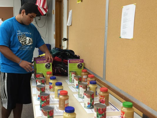 Michael Contreras, 16 helps at Rapids Family Backpacks in 2014