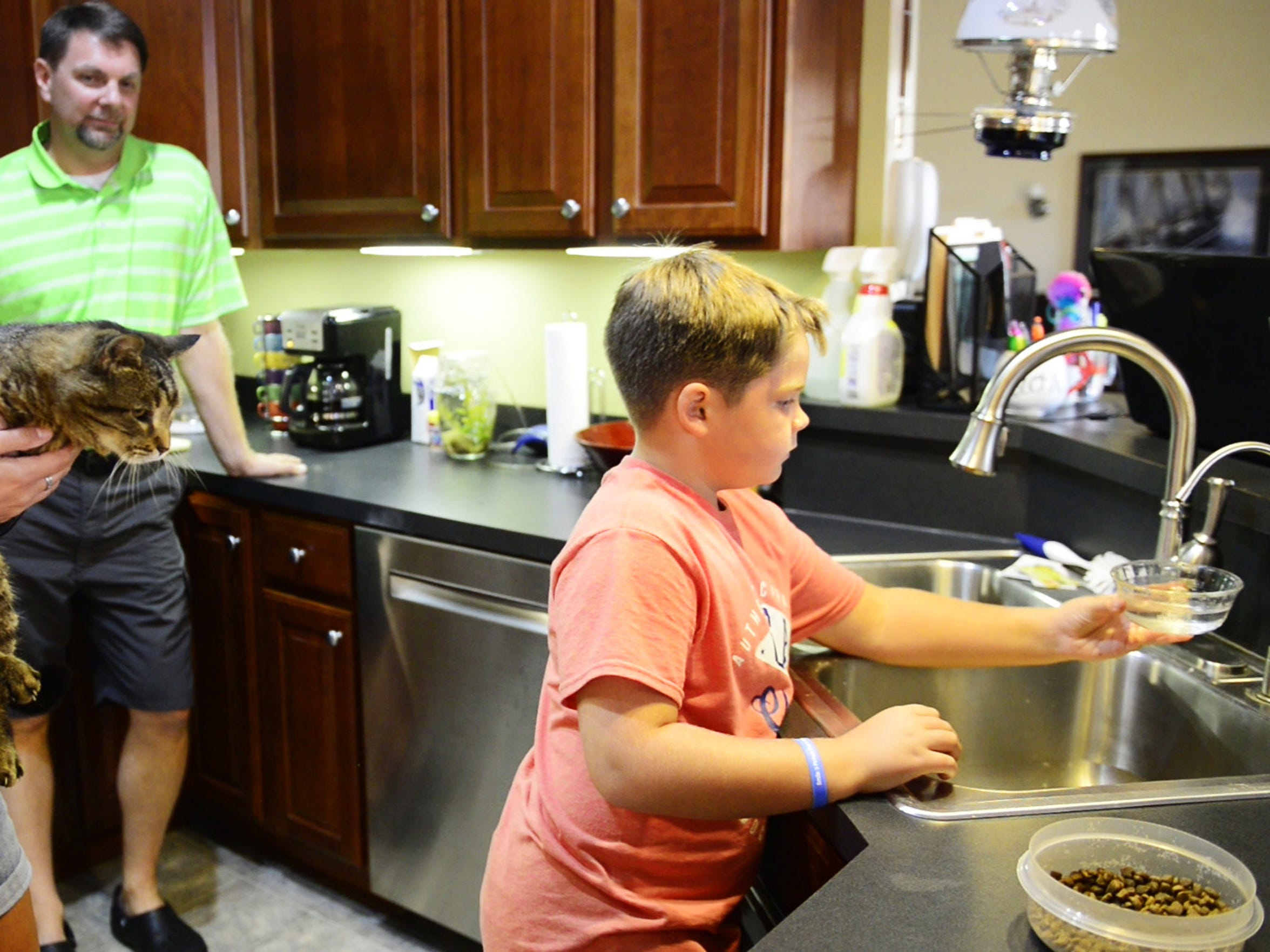 From left, Christy and Josh Noble and their son, Henry, 9, give their cat Oscar a drink of water from their well.  The Nobles own a home on Toussaint North Road in Benton Township and are worried about their water well, which is only a few hundred yards away from Rocky Ridge Development LLC's quarry operation.