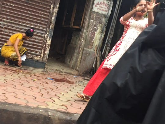 A woman along Falkland Road in Mumbai, India, makes a circle with a thumb and finger and rapidly thruststheindex finger of her other hand in and out. This area is known for its public brothels.