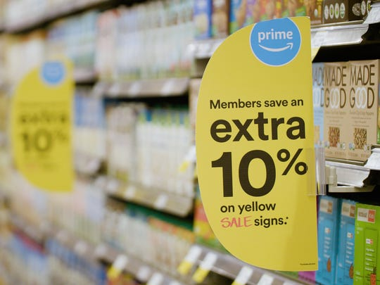 Yellow sale signs at Whole Foods with the Prime logo indicate extra discounts for shoppers.