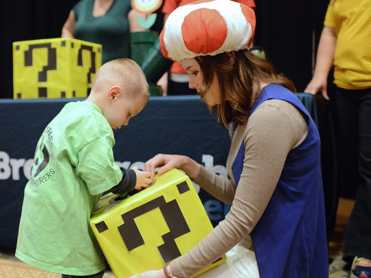 Dressed as Toad, Erin McGinley offers up the box of unknown prizes to Eli Pukel, 3, to draw from at Breakthrough Fuel's booth themed after the Super Mario franchise. The Brown County United Way Emerging Leaders Society hosted Fall Fest, an opportunity for more than 100 children to have Halloween themed fun at The Meadows.