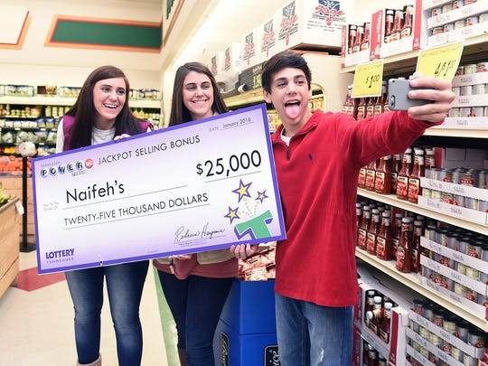 Ally, Abby and Oney Naifeh take a selfie with their family's Tennessee lottery check that was presented at their family's store, Naifeh's Food Mart, on Thursday Jan. 14, 2016, in Munford, Tenn. The store received the money for selling one of the three winning Powerball lottery tickets.