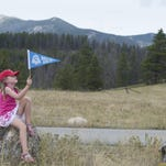 Caroline Joseph, 5, visiting from Wichita, Kansas with her family, waves a pennant to celebrate the rededication ceremony marking Rocky Mountain National Park's 100th anniversary Friday.