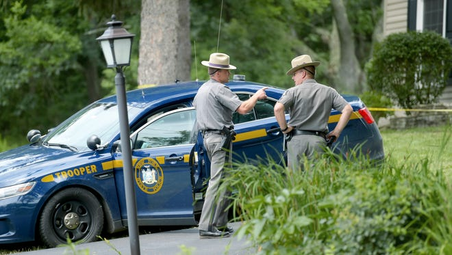 Law enforcement officials investigate the scene of a shooting which claimed the life of New York State Trooper Nicholas Clark. The incident at 10041 Welch Road in the Town of Erwin, near Corning, occurred early Monday morning. The suspect, Steven Kiley, was barricaded inside the residence and was later found dead of a self-inflicted gunshot wound.