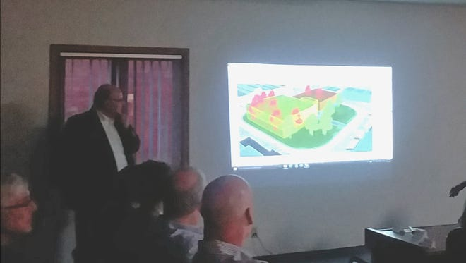 Mike Lewis of Shive-Hattery shows a picture of what new courthouse and jail buildings would look like on the Indianola Square.