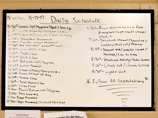 A daily schedule is posted on the wall of a dormitory