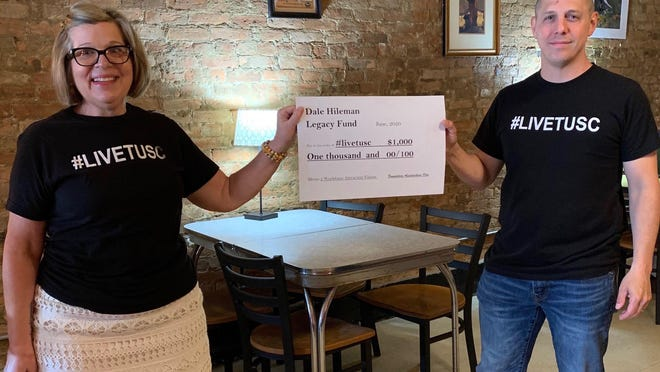 Diane Lautenschleger of the  Tuscarawas County Convention and Visitors Bureau and Jason Ricker of the Tuscarawas County Economic Development Corp. hold up a grant check that Tuscarawas Valley Heritage Inc. received from the Dale Hileman Legacy Fund.