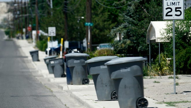 A row of trash cans lines West Blanco Street on Thursday in Bloomfield, where waste disposal services are offered by the WCA Waste Corporation.
