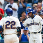 Seattle Mariners' Austin Jackson, right, greets Robinson Cano at home plate after scoring on a two-run home run by Cano against the Chicago White Sox during the fifth inning of a baseball game Sunday, Aug. 23, 2015, in Seattle.