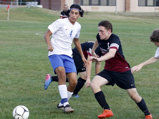 Robert McCarrick of Elmira chases the ball in front of Horseheads' Chris Enright during boys soccer Wednesday at Horseheads.
