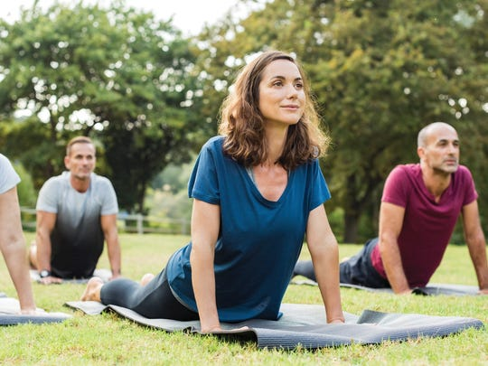 Mature healthy people doing yoga at park.