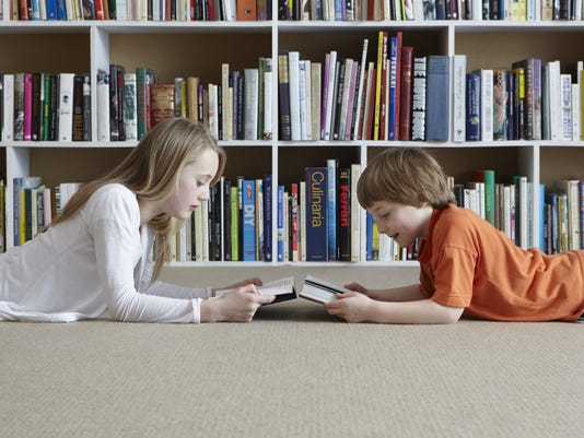 Children reading by bookshelves
