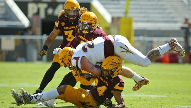Arizona State Sun Devils running back Mark Cosgrove gets stopped by defensive back Chase Lucas during their spring football game Saturday, April 15, 2017 in Tempe, Ariz.