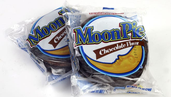 """The MoonPie was born in 1917 when a Kentucky coal miner asked a Chattanooga Bakery traveling salesman if he could sell him a snack """"as big as the moon."""" He went back to the home office, and bakers created a marshmallow and graham cracker sandwich enrobed in chocolate."""