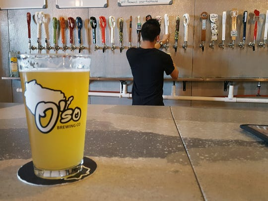 Bartender Johnny Yang pours a beer at the O'So Brewing Co. Tap House in Plover, south of Stevens Point.