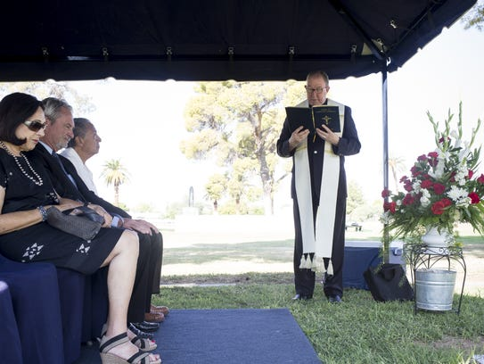 The Rev. Dan Sullivan says a prayer during a headstone