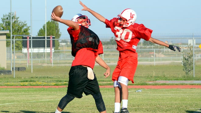 Loving's Kevin Gut-Omen throws the ball with Cruz Ornelas right in his face during Wednesday's practice. The Falcons open district play tonight at Dexter.