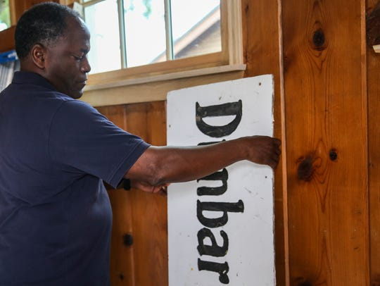 Ronnie Hawkins moves the original sign of the Dunbar