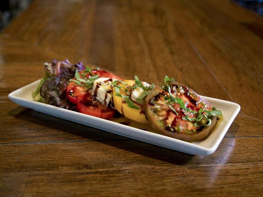 Cool dishes like the heirloom tomato caprese salad are summer specials at Thirsty Lion.