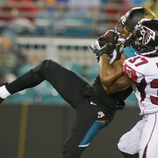 Aug 28, 2014; Jacksonville, FL, USA; Jacksonville Jaguars wide receiver Mike Brown (12) catches a pass as Atlanta Falcons cornerback Ricardo Allen (37) defends in the fourth quarter of their game at EverBank Field. The Atlanta Falcons won 24-14. Mandatory Credit: Phil Sears-USA TODAY Sports