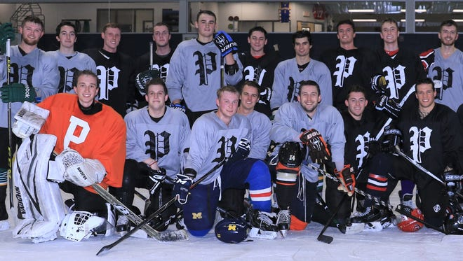 "Plymouth High School's varsity boys hockey program held a ""Gray-vs.-Black"" alumni game Dec. 28 at Arctic Edge Arena in Canton. Players and head coach Gerry Vento (standing, far right) pose for the group photo following the contest."
