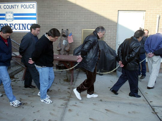 Reputed members of the Lucchese crime family are walked out of the 3rd Precinct Police stationhouse in Bay Shore, New York, on Nov. 14, 2002.