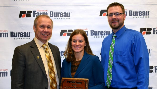 Mason Rens and his wife, Andrea Brossard accept the Wisconsin Farm Bureau Federation's Young Farmer and Agriculturist Achievement Award from President Jim Holte, left, during the organization's 97th annual meeting Dec. 4 in Wisconsin Dells.
