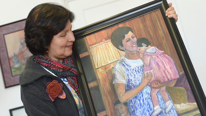 "Rosa Luz Catterall holds a painting she created based on a photograph of her when she was 7-months pregnant with her youngest son, Anthony. She is holding her daughter Christine, while her older son, William, stands behind her. The painting is called ""A Mother's Light."""