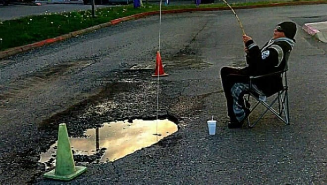 Jerry Hinds pretends to fish in a pothole in a parking lot near Lund Avenue.