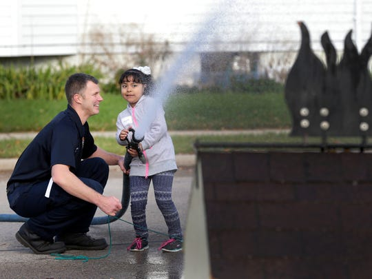 Banta Elementary School student Joyelle Ariaga Flor, 6, holds on tight as firefirghter Mike Pokwinski assists her in putting out a simulated fire during a kid day event Wednesday, October 21, 2015, at the Neenah-Menasha Fire Rescue Fire Station NO. 32 in Neenah, Wis. According to office manager Tara Theisen, the Fire Prevention and Education team performs fire prevention safety to all children in grades 1-3 in all public and private schools in the Neenah and Menasha joint school districts. The kids enter a drawing to spend the morning at the fire station. Each school chooses two children to attend to have a pancake breakfast and perform activities that teach them what it's like to be a firefighter.