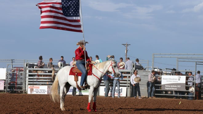 A member of the Will Rogers Ranger Riders Drill Team carries the American Flag to open the 78th Annual Will Rogers Range Riders Rodeo Thursday evening.