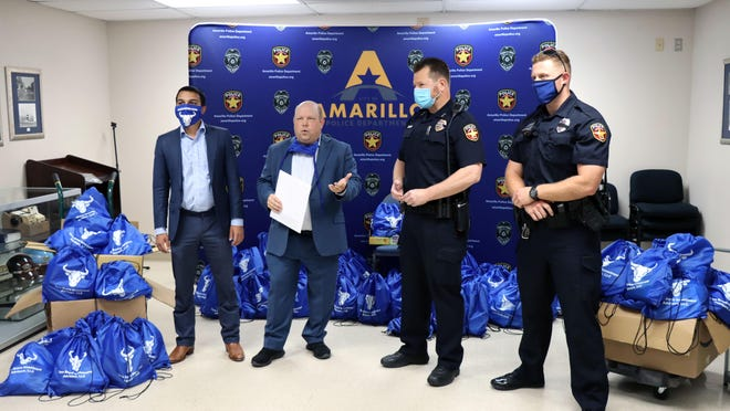 Mubashir Subhani and Brian Moon with Toro Bravo Investment Advisors present gift bags to Chief Jimmy Johnson and Officer Casey as appreciation for the Amarillo Police Department's service to the community on Tuesday at the police station.