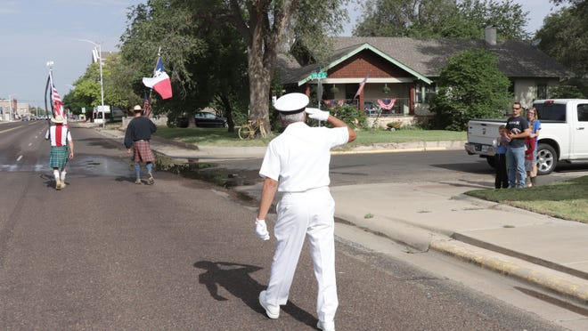 """Eloy Heras (Navy Veteran) salutes the Redekop family, which stoppped to say thank you, as James Smith (Army Veteran) and Stephen """"Boats"""" Arthur (Navy Veteran) and Eloy celebrated the Fourth of July by carrying the American and Texas State Flags on the normal route of the canceled Canyon parade Saturday morning."""