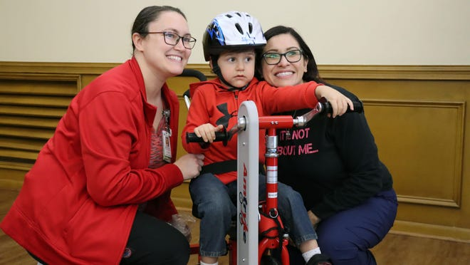 Zaiden Martinez (center) sits on his new amtryke from Southwest AMBUCs for a picture with his therapist Maegan Harder and mother Stephanie Martinez.