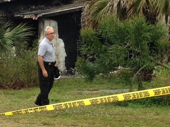 A fire investigator looks over damage to a home on Dortch Avenue in Bonita Springs where a woman and a family pet died Tuesday morning.