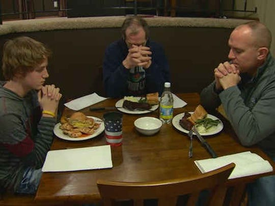 William Tentis, middle, leads a dinner prayer at the