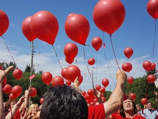 Members of St. Paul Lutheran Church release red balloons