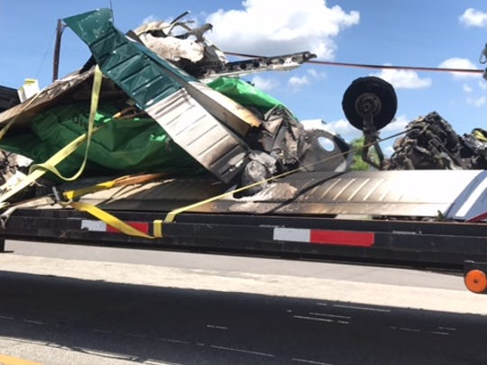 Wreckage of a private plane that crashed on take off at Page Field on Saturday is carted away by the National Transportation Safety Board for examination.