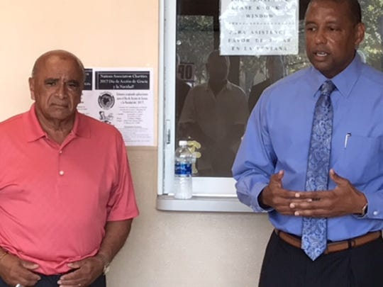 Israel Suarez, founder and creator of Nations Association charity, listens as Marcus Goodson, executive director of the Housing Authority of Fort Myers, talks about the non-profits $10,000 donation for hurricane relief.