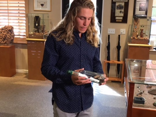 Wes Skinner shows the certificate he found in a bottle in the Gulf of Mexico that won him a $10,000-plus retail diamond, part of a Valentines Day promotion by Mark Loren Designs.