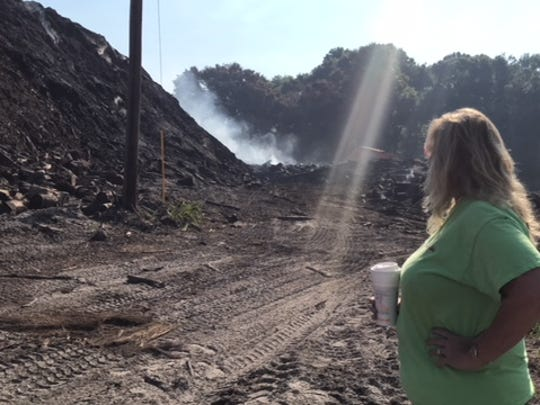 In this file photo, Denise Houghtaling, owner of MW Horticulture Recycling, watches smoke drifting from a fire at the company's property on East Street in North Fort Myers.  Much of the mulch on the site has been removed, but not fast enough to the Lee County hearing examiner which is now imposing $200 per day fines until the property complies with county ordinance.