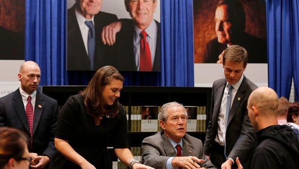 Former President George W. Bush signs books.