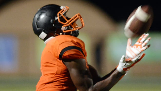 Jamel Dean catches a pass during Friday's game at Cocoa Stadium.