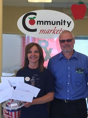 """Community Market Cashier Korilee Hatmaker and Manager Lester Weatherwax receive the prize basket worth over $200 for selling the most """"stars"""".."""